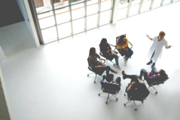 abstract blurred defocused of asian young team sitting group circle meeting in top wide angle view in modern office. asian speaker explain, teach, coach, sharing idea to audience in education concept. - training imagens e fotografias de stock