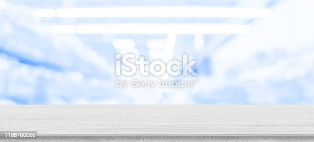 abstract blurred drug store aisle shelf distribution background with white wood perspective counter to show,promote ans advertise products on display for medical pharmaceutical business concept