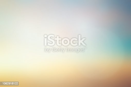istock abstract blurred early sunlight of teal and gold color sky background with lens flare light for design element as banner , presentation 1062918122