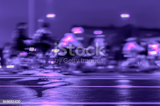 929609038istockphoto Abstract blurred group of bicyclists on city street, lights on night, urban scene, violet background, intentional motion. Sport, fitness, healthy lifestyle concept 948683400