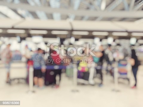 istock Abstract blurred image background of group people or arriving passengers with their suitcases and luggage walking in international  airport terminal, travelling or business concept. vintage tone. 938016366