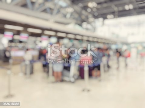 istock Abstract blurred image background of group people or arriving passengers with their suitcases and luggage walking in international  airport terminal, travelling or business concept. vintage tone. 938016386