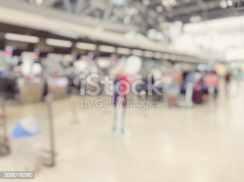 istock Abstract blurred image background of group people or arriving passengers with their suitcases and luggage walking in international  airport terminal, travelling or business concept. vintage tone. 938016390