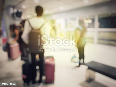 istock Abstract blurred image background of group people or arriving passengers with their suitcases holding luggage walking in international  airport terminal, travelling or business concept. vintage tone. 938016522