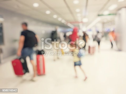 istock Abstract blurred image background of group people or arriving passengers with their suitcases holding luggage walking in international  airport terminal, travelling or business concept. vintage tone. 938016542