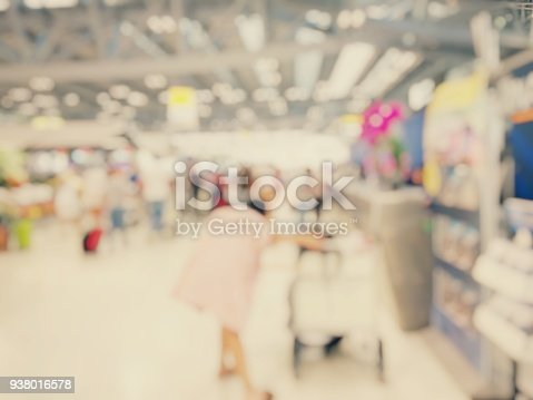 istock Abstract blurred image background of group people or arriving passengers with their suitcases holding luggage walking in international  airport terminal, travelling or business concept. vintage tone. 938016578