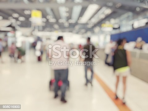 istock Abstract blurred image background of group people or arriving passengers with their suitcases holding luggage walking in international  airport terminal, travelling or business concept. vintage tone. 938016900