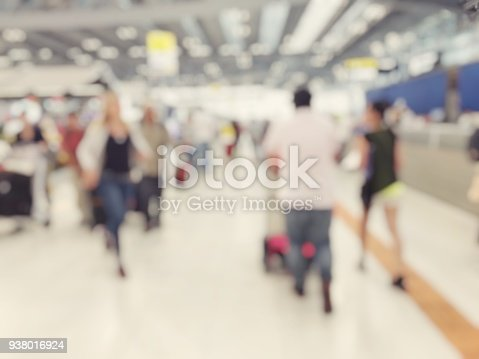 istock Abstract blurred image background of group people or arriving passengers with their suitcases holding luggage walking in international  airport terminal, travelling or business concept. vintage tone. 938016924