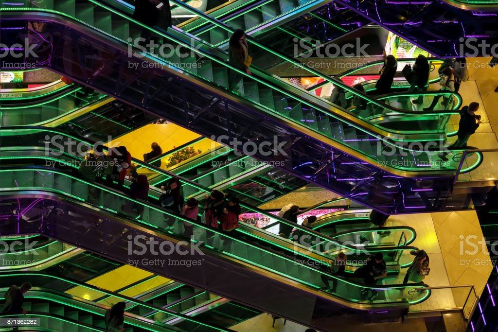Abstract blurred image of modern shopping mall, unrecognizable silhouettes of people on escalators, modern background for design. Motion effect stock photo