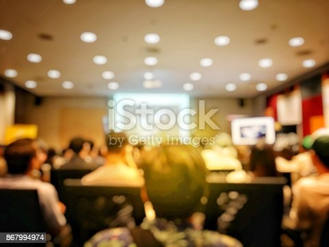 478810450 istock photo Abstract blurred image of people sitting in conference room for profession seminar with attendee, presenter and audience background, business & educaction concept, official new product launches 867994974