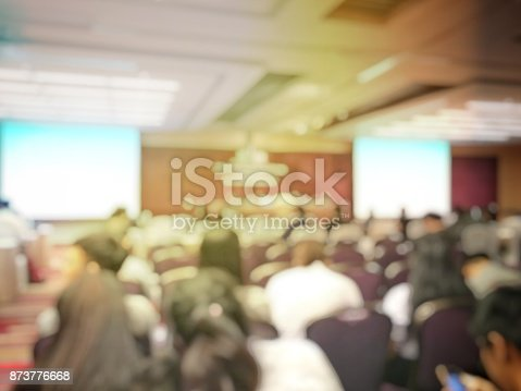 Abstract blurred image of people sitting in conference room for profession seminar with attendee, presenter and audience background, business & educaction concept, official new product launches