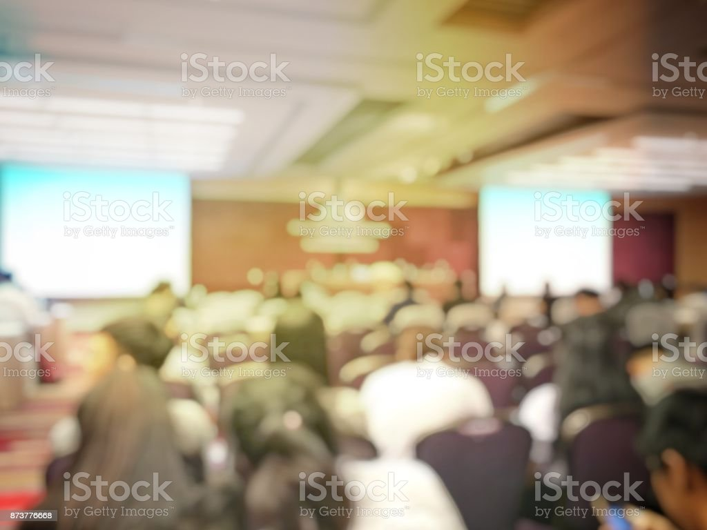 Abstract blurred image of people sitting in conference room for profession seminar with attendee, presenter and audience background, business & educaction concept, official new product launches stock photo