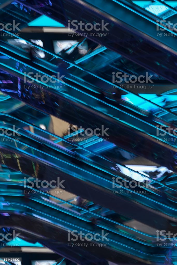 Abstract blurred image of shopping mall, recognizable silhouettes of people on escalators with neon backlight, modern background for design. Motion effect stock photo