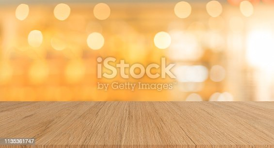 istock abstract blurred inside interior of luxury restaurant with light bokeh bulbs and modern wood table background for ads,show,promote product design concept 1135361747