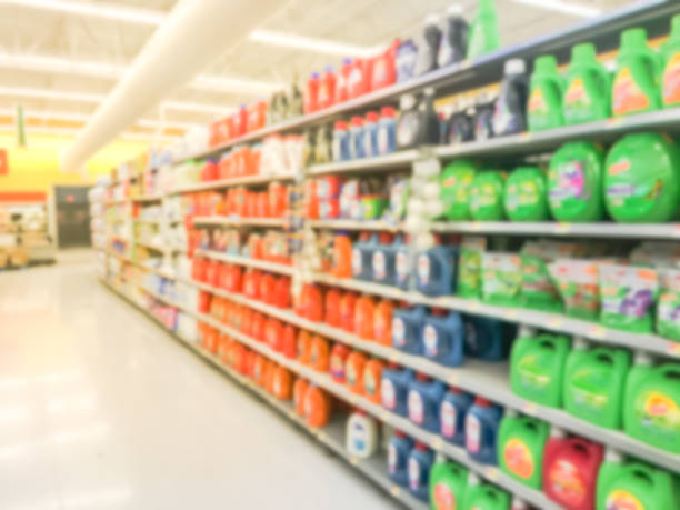 Abstract blurred laundry detergent products at retail store in USA Blurred abstract bleach, fabric softener, laundry detergent, all purpose cleaners shelves in modern grocery retail store. Defocused variety of cleaning, grocery, household aisle from floor to ceiling laundry detergent stock pictures, royalty-free photos & images