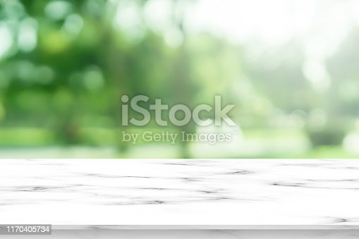 abstract blurred leaves of tree in nature forest with sunny and bokeh light  at  public park background with white marble pattern tabletop for show, promote ads and design product on display concept
