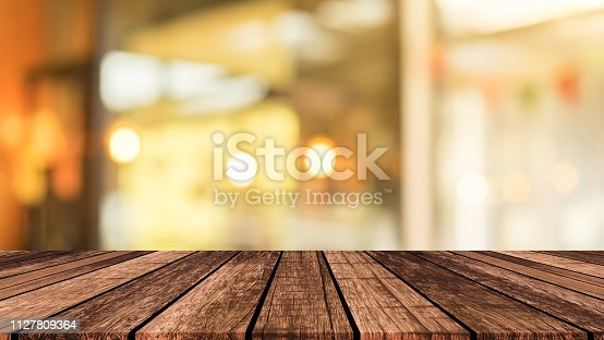 abstract blurred modern interior coffee cafe shop decorate with bulbs lamp light on ceiling and wood counter table perspective for show, promote, advertise product o display montage concept