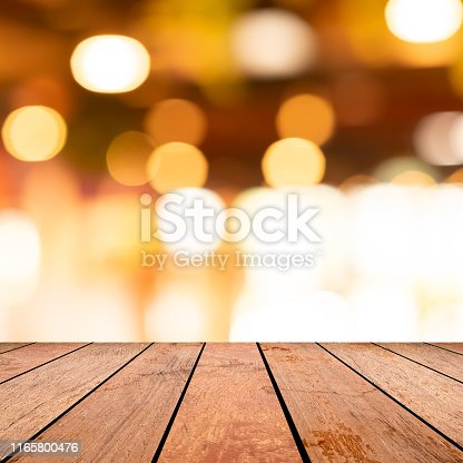 864907996istockphoto abstract blurred modern interior restaurant cafe shop decorate with bulbs lamp light on ceiling and vintage wood counter table perspective square background for show, promote, advertise product on display montage concept 1165800476