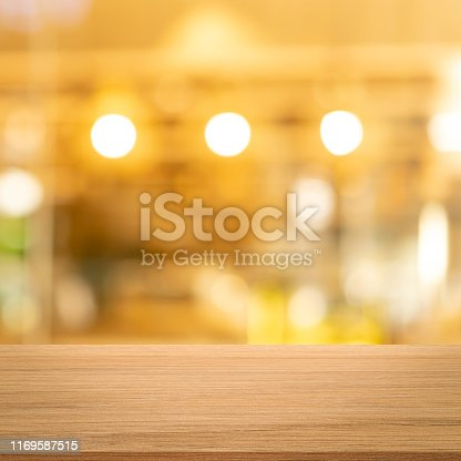 864907996istockphoto abstract blurred modern interior restaurant cafe shop decorate with bulbs lamp light on ceiling and wood counter table perspective square background for show, promote, advertise product on display montage concept 1169587515