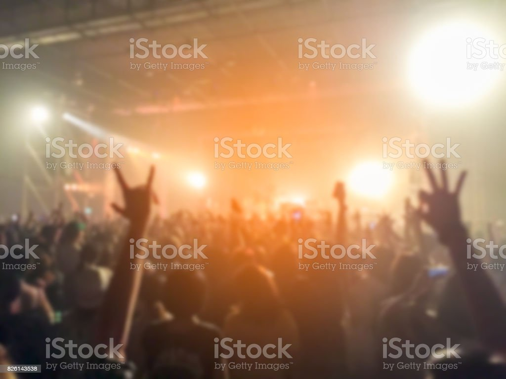 Abstract blurred of concert with hands up having fun
