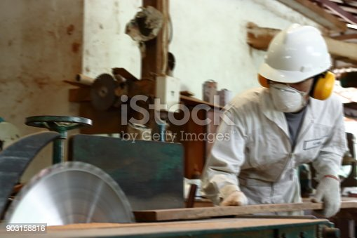 1152920014 istock photo Abstract blurred of professional young carpenter with safety equipment cutting a piece of wood on table saw machine in carpentry factory. 903158816
