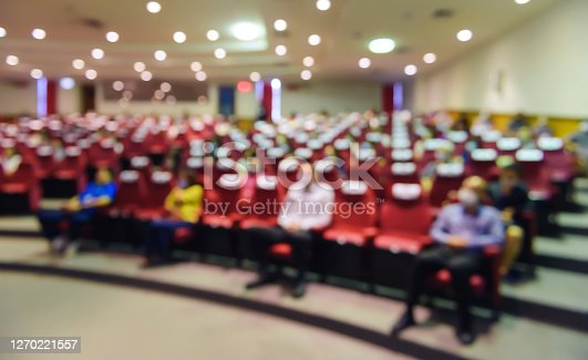 Abstract blurred of put spaces between attendee in seminar room or conference hall for social distancing to prevent the spread of Covid-19. new normal life concept.
