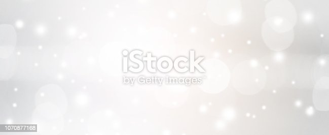 istock abstract blurred of silver color with bokeh and glitter snow fall background for design concept. 1070877168