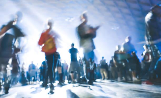 Abstraits gens floues passant et danse à la musique nuit événement festival - défocalisé image du parti de la discothèque avec show laser - vie nocturne entertainment concept - filtre spotlight contraste bleu azur - Photo