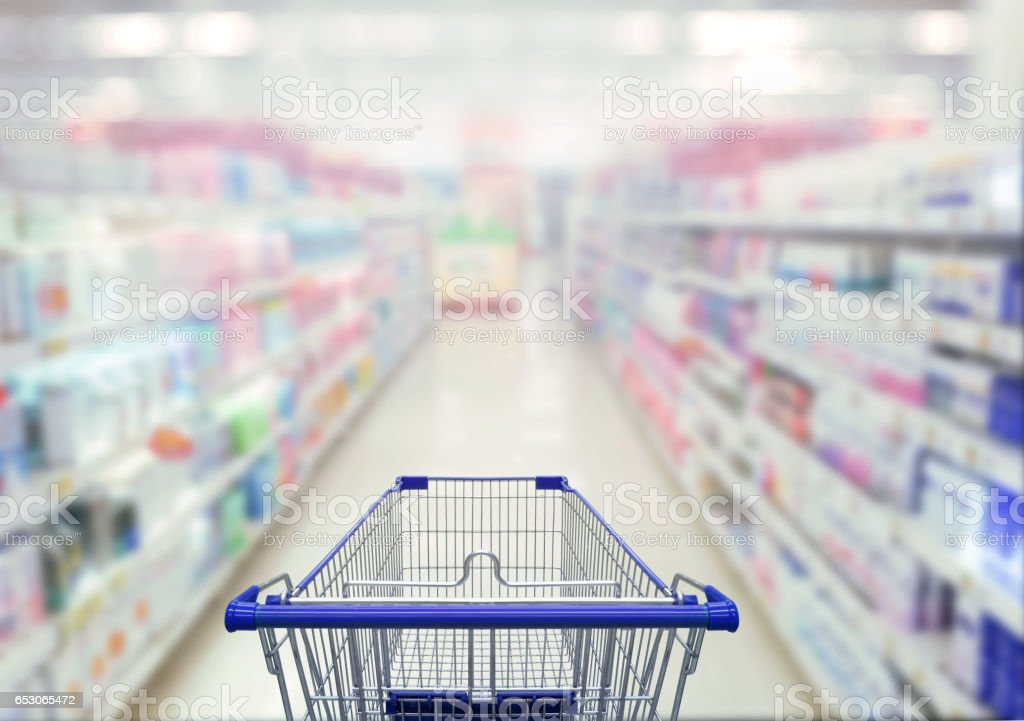 Abstract blurred photo of  cosmetic area in supermarket with empty shopping cart shopping concept. stock photo