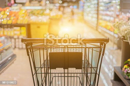 istock Abstract blurred photo of trolley in department store bokeh background,empty shopping cart in supermarket ,vintage color 981318622