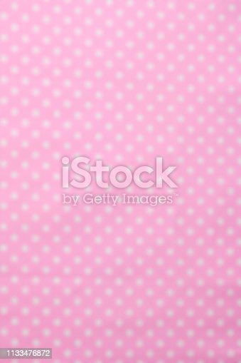 Close-up of abstract blurred polka dot fabric texture background.