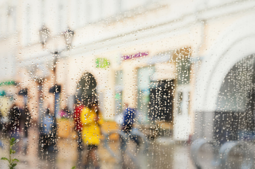 istock Abstract blurred silhouettes of people after rain in the city, girl in yellow seen through raindrops on window glass, blurred background. Concept of modern city 695633488