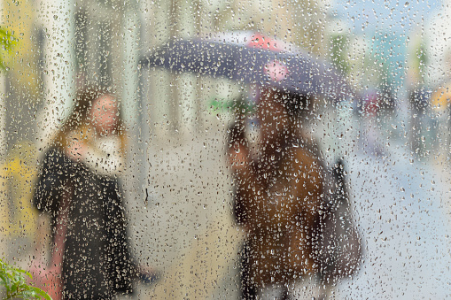 istock Abstract blurred silhouettes of people with umbrellas on rainy day in city, two girls seen through raindrops on window glass, blurred background, backdrop, wallpaper 695633184