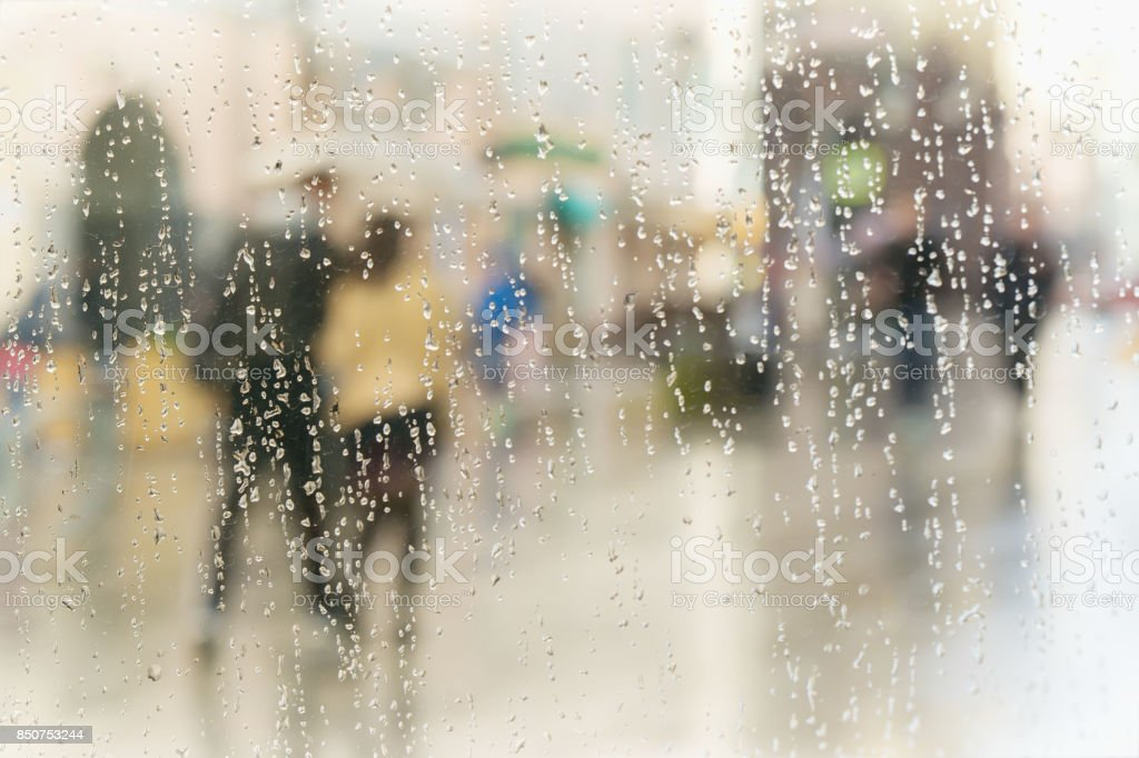 Abstract blurred silhouettes of people with umbrellas on rainy day in...