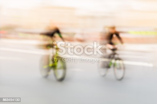 863454090istockphoto Abstract blurred sport backdrop of of two cyclists in the city street. For modern background, wallpaper or banner design, place for your text 863454130