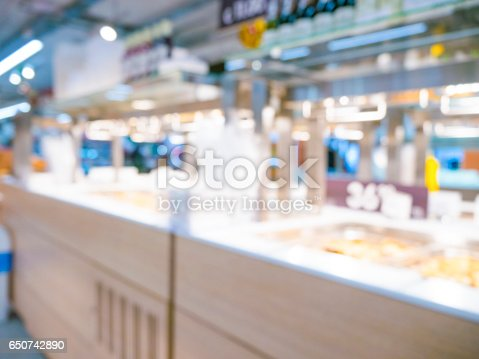 968898244 istock photo Abstract blurred supermarket aisle with colorful shelves and unrecognizable customers as background 650742890