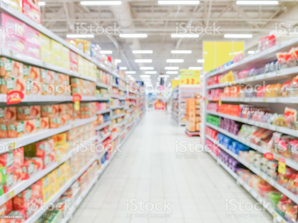 Abstract blurred supermarket aisle with colorful shelves and unrecognizable customers as background stock photo