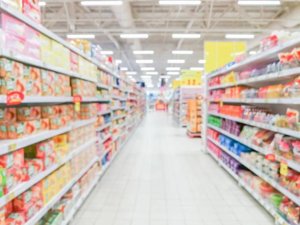 Allée de supermarché floue abstraite avec étagères colorées et clients méconnaissables comme toile de fond - Photo