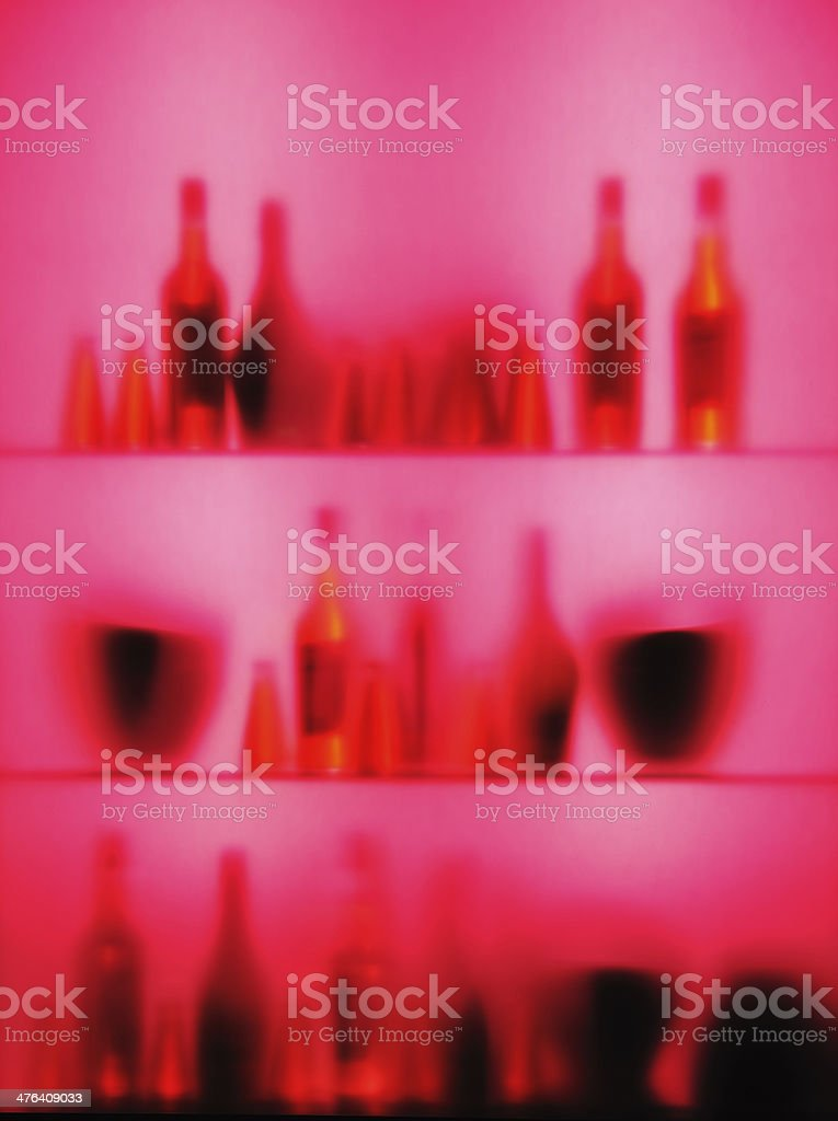 Abstract blurred vine bottles and glasses on shelf, pink color royalty-free stock photo