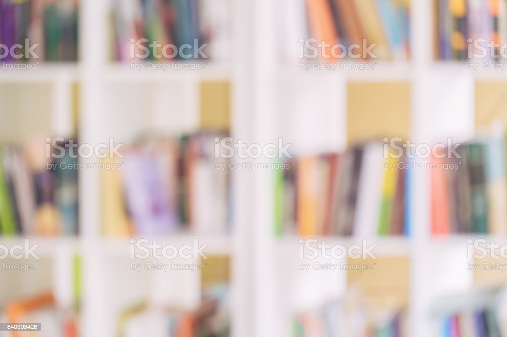 Abstract blurred white bookshelves with books, manuals and textbooks...