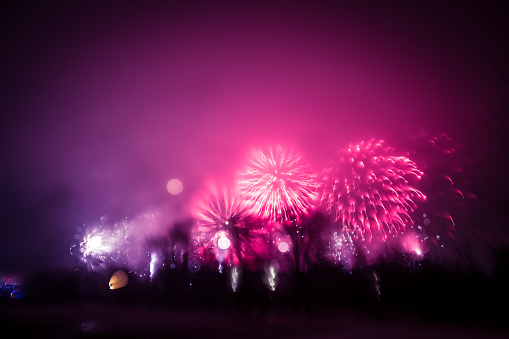 Abstract, blurry, bokeh-style colorful photo of fireworks in a purple tone above the river
