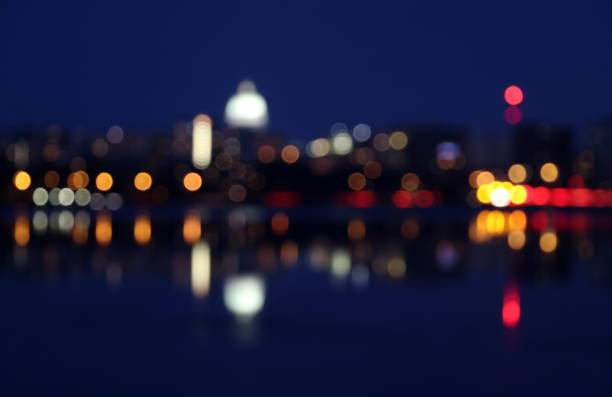 Abstract booked night city lights background. Silhouette of Madison skyline at night with out of focus street lights and glowing in the dark state Capitol building reflected in a lake water during twilight. Wisconsin, Midwest USA. dane county stock pictures, royalty-free photos & images