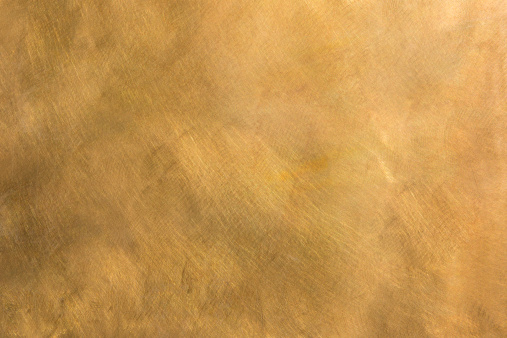 Brushed brown-golden copper or bronze surface, with visible brush strokes. The sheet metal has an appealing cloudy, wavy texture. Horizontal orientation. The image has been shot outdoors during natural day light, full frame and close up. Ideal for backgrounds. The dimensions of the photo are 5040 x 3360 px. High resolution.