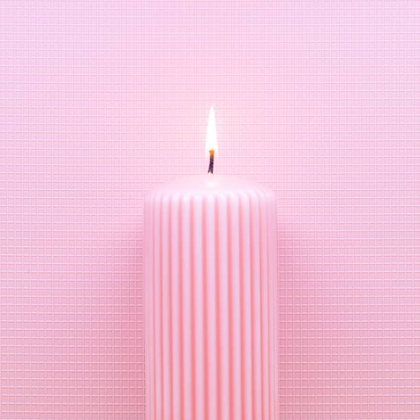 abstract burning candle on pink background. Minimal flat lay Christmas or Birthday theme. stock photo