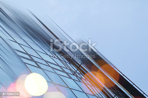 istock Abstract business modern city urban futuristic architecture background. Real estate concept, motion blur, reflection in glass of high rise skyscraper facade, toned blue picture with bokeh 877064774