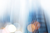 istock Abstract business modern city urban futuristic architecture background. Real estate concept, motion blur, reflection in glass of high rise skyscraper facade, toned blue picture with bokeh 878650066