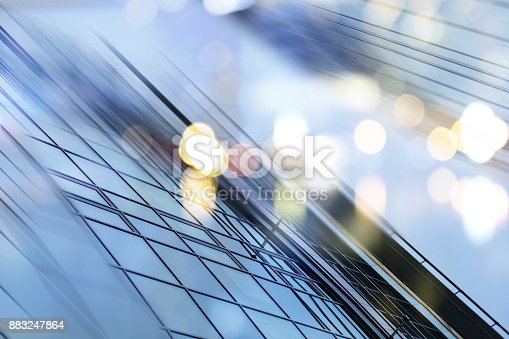 istock Abstract business modern city urban futuristic architecture background. Real estate concept, motion blur, reflection in glass of high rise skyscraper facade, toned blue picture with bokeh 883247864
