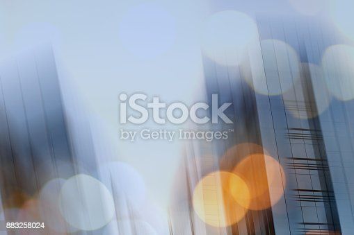 istock Abstract business modern city urban futuristic architecture background. Real estate concept, motion blur, reflection in glass of high rise skyscraper facade, toned blue picture with bokeh 883258024