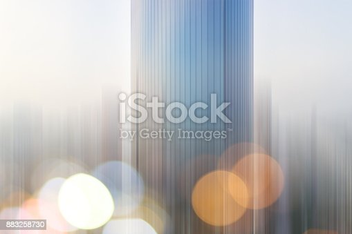 istock Abstract business modern city urban futuristic architecture background. Real estate concept, motion blur, reflection in glass of high rise skyscraper facade, toned blue picture with bokeh 883258730