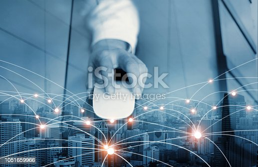 istock Abstract. Businessman using mouse global network and data exchanges customer connection on city scape background. Blue tone. Technology business and digital networking concept. 1051659966